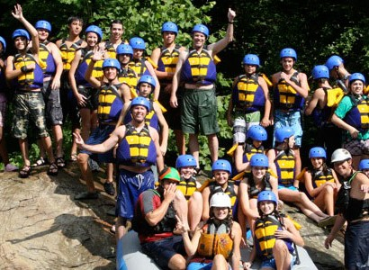 Youth Group Huddles on Rock before Whitewater Rafting Trip with Raft One | Raft One